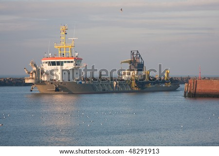 A small dredger entering a harbor