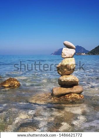A small equilibrium rock tower in the water of the ionian seas. Waves and sunny weather.