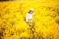 A small, fair-haired girl, standing in a yellow, blooming field, holding a green net in her hands. Image with selective focus. The image is tinted. The image contains noise.