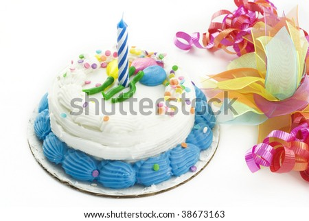 A small first birthday cake decorated with white and blue frosting with sprinkles, one unlit birthday candle, colored ribbon decorations, isolated on white background with copy space