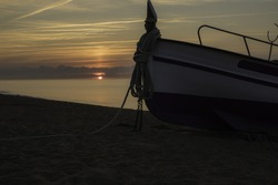 A small fisher boat on a dreamlike beach touched by the first sunrays