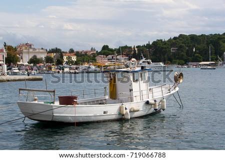 A small fishing boat in small marina.