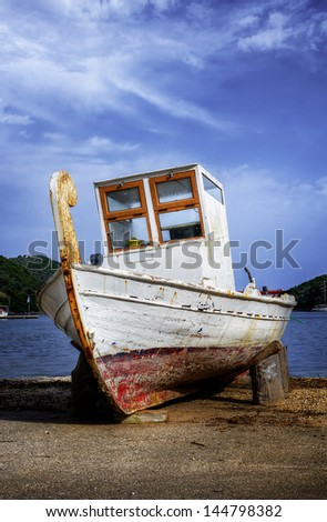 A small fishing boat out of the water, for repairs, in Syvota village, Lefkada island, Greece