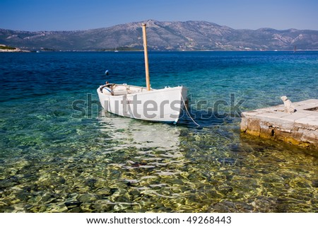 A small fishing boat tied into harbour on a beautiful sea
