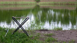 A small fishing chair for one person stands on the grass next to the lake. Next to it is a fishing rod. Fishing concept.