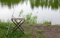 A small fishing chair for one person with a military print stands on the grass next to the lake. In the lake, the reflection of trees covered with green foliage. Fishing concept.