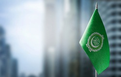 A small flag of Arab League on the background of a blurred background