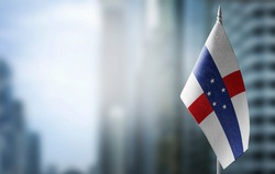 A small flag of Netherlands Antilles on the background of a blurred background