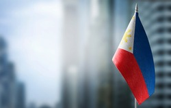 A small flag of Philippines on the background of a blurred background