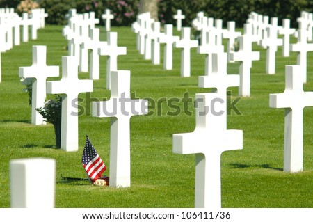A small flag of the US between cross headstones at the American military cemetery in the Netherlands