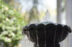 A small fountain in the backyard. To decorate the garden with water in the area of the house.