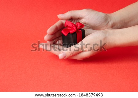 Photo of  A small gift box with a red ribbon on a bright red background. Women's hands hold a gift. Christmas, February 14, birthday. Focus on the gift.