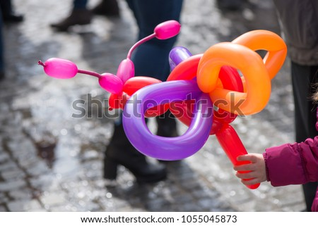 A small girl holding a balloon butterfly or dog that she got as a gift for her birthday party at a children party from clown