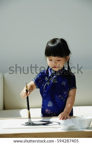 A small girl in blue silk cheongsam writing Chinese calligraphy #594287405