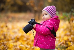 A small girl is photographer, kid holds a camera and takes photo of autumn landscape, child stands in the autumn park and girl is dressed in warm hat and jacket.