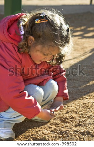 A small girl playing with sand in the playground.