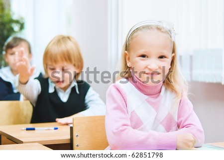 A small girl sits at the desk