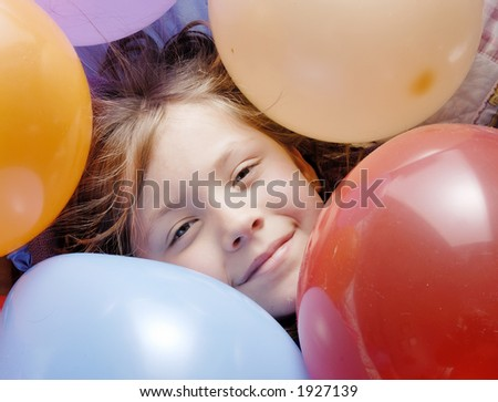 a small girl surrounded with balloons