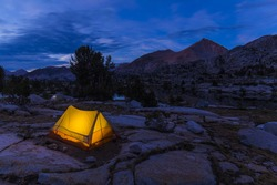 A small glowing tent sits in an alpine basin with lake and pine trees surrounded by tall bare granite peaks in California