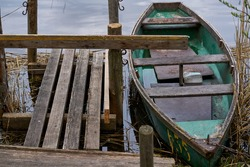 A small green boat floating on the lake near the pier.