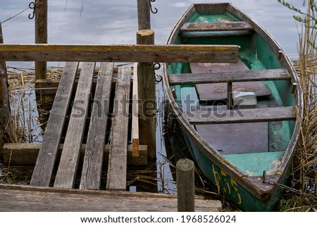 A small green boat floating on the lake near the pier. Foto d'archivio ©