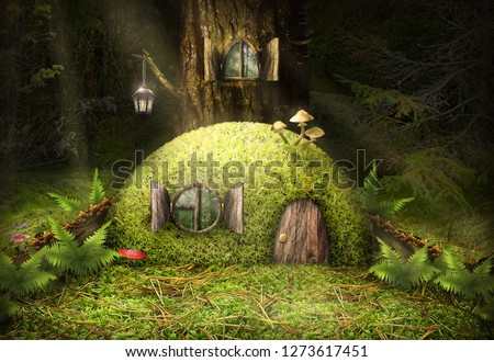 A small green house in the woods near a tree with a round window with a fern and mushrooms.