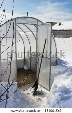 A small greenhouse in winter is empty