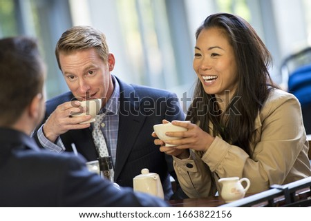 A small group of people, a businesswoman and two businessmen sitting in a coffee shop having a cup of coffee. Сток-фото ©