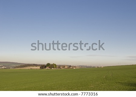 A Small Hamlet in the Medway Valley Across Green Fields with a Clear blue sky. A little pollution Haze lies in the valley