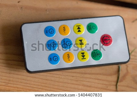 A small handheld remote controller device with colorful buttons to press #1404407831
