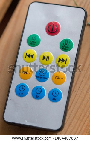 A small handheld remote controller device with colorful buttons to press #1404407837