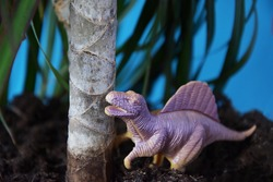 A small herbivorous dinosaur under a palm tree, under a tree. Dinosaur Model - Extinct Jurassic Animal, Paleontology.