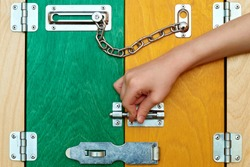 A small human hand closes colored bright wooden doors on a metal latch and bolt. A child protects his home
