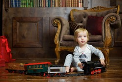 A small infant boy sits on the floor and plays a clockwork train. Games and activities for children.