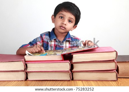 A small kid looks while reading big old books