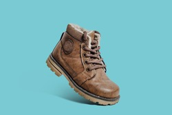 A small leather shoe isolated on a green, pastel background. Shoe on a blue background. Warm and fur-lined children's shoe with laces. Concept of the coming autumn and winter.