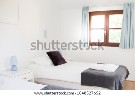 a small little single bed in bedroom with windows in sun #1048527652