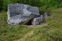 a small manhole covered with a large limestone boulder, the entrance to the cave