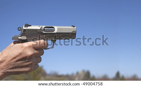 A small 9mm handgun pointed and ready to fire. - stock photo