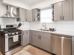 a small modern kitchen with grey cabinets
