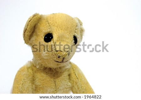 A small old worn teddy bear isolated on near white