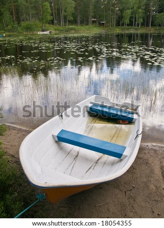 A small open boat on the shore of a small lake.