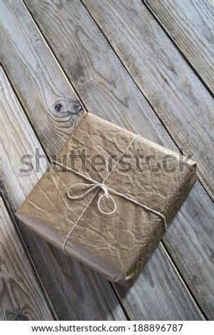 A small package wrapped in recycled brown paper which is tied with a cord. The package is over weathered wood.