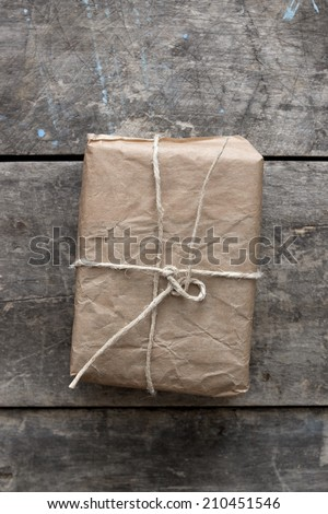 A small package wrapped in recycled brown paper which is tied with a white cord. The package is lying on weathered wood.