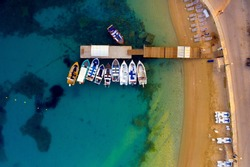 A small peer with boats on a beach aerial. Beautiful torquoise waters of mediterranean sea. Boat parked near island