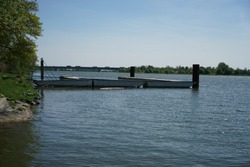A small pier by the lakeshore, waterscape in the background