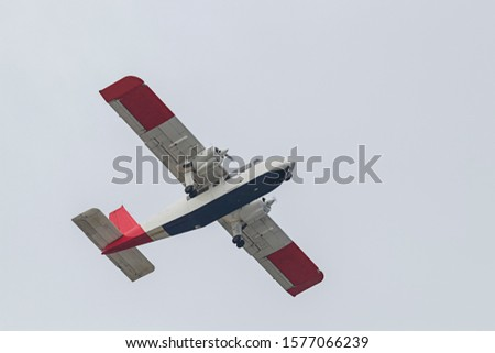 A small plane takes off and takes off on the island of Dune. Background is bright sky