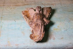 A small plaster sculpture of an angel on the wall