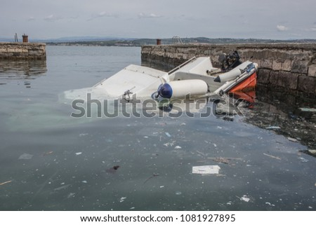 A small plastic boat partially sunk under water in a small marina close to a port of Koper in Slovenia. Debris or trash is seen floating in the water.