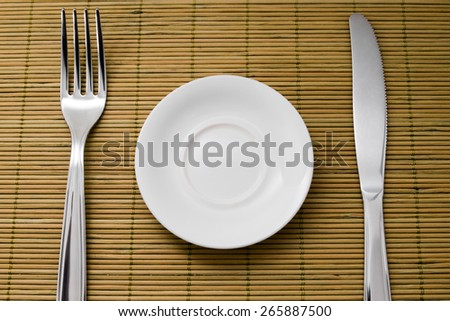 A small plate for diet next to a knife and fork on green bamboo placemats